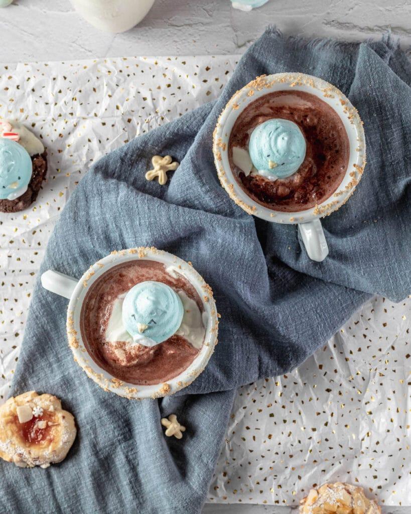 penguin meringue cookies floating in hot chocolate